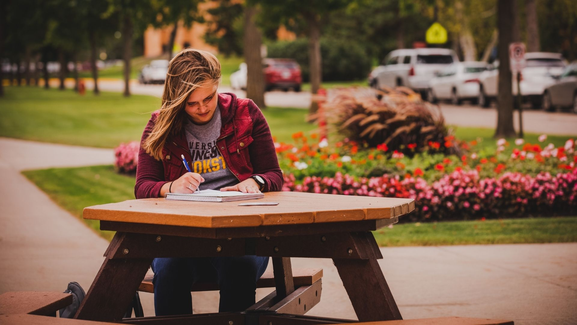 student reading at picnic table