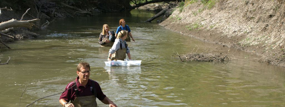 Teacher and students walking in a river getting samples