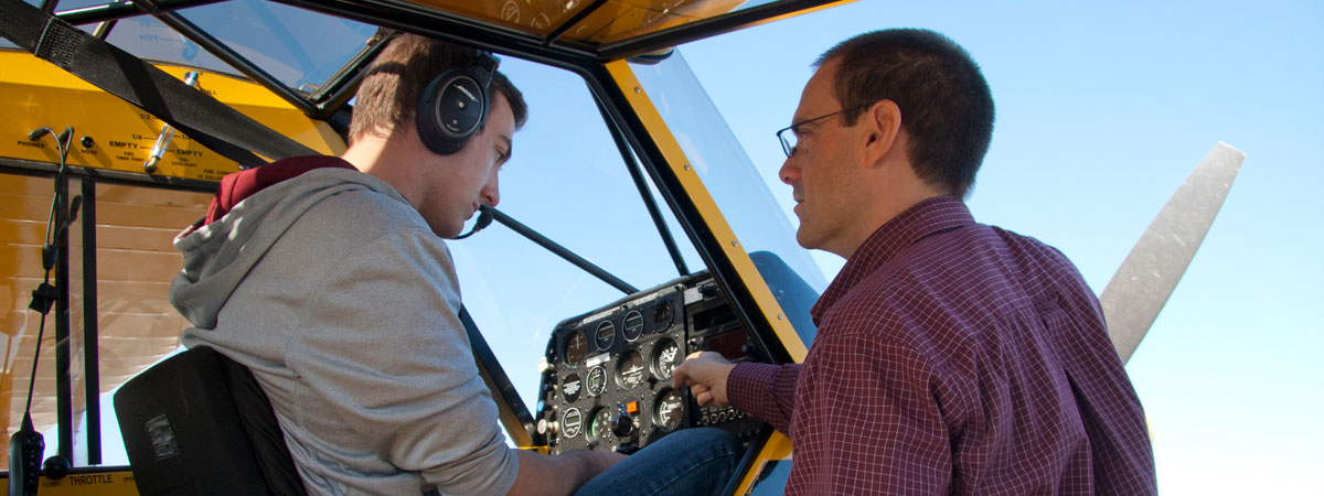 A teacher instructing a student on the controls in the plane
