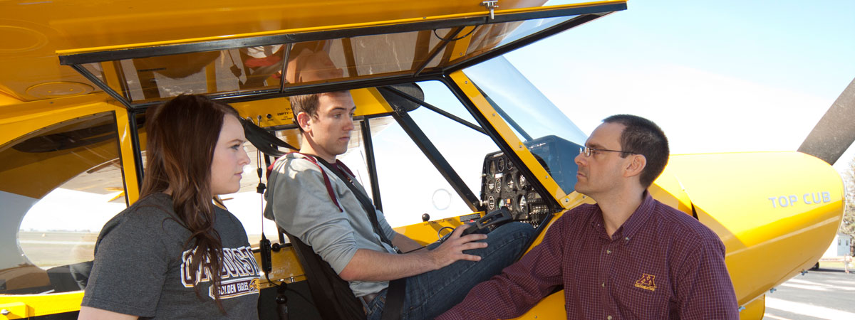 Two students being instructed by a teacher about planes