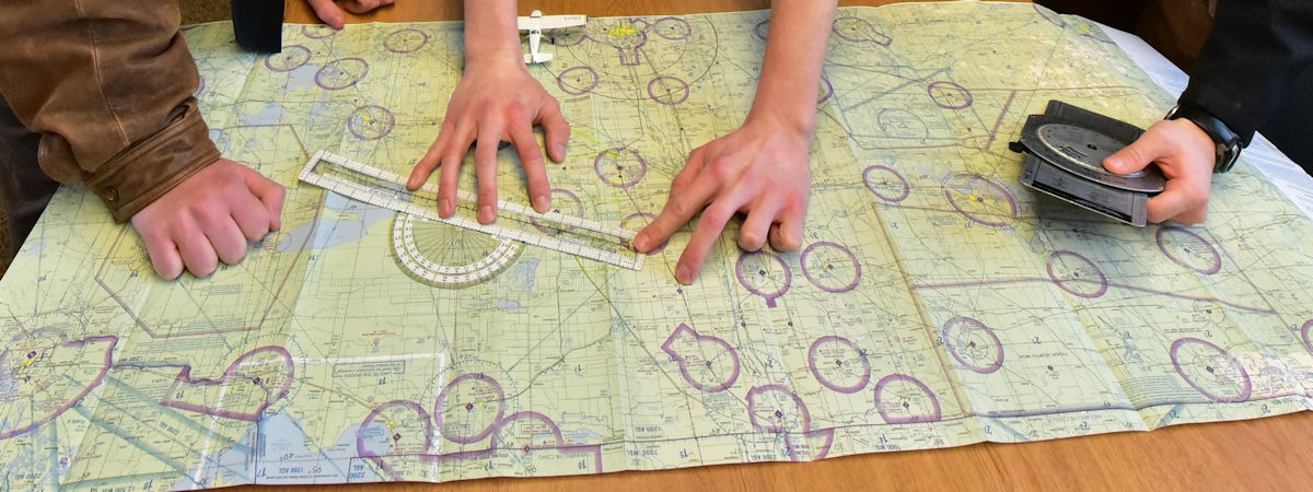 hands working on a flight course map