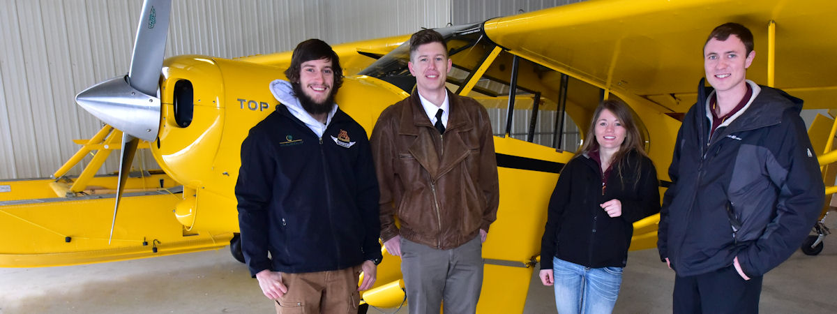 Three students with flight instructor standing by plane