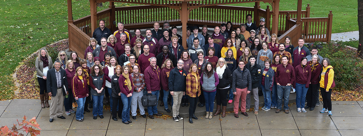 Group photo of UMC faculty, staff and students on a cool, rainy, fall day outside Peterson Gazebo on the UMC Mall.