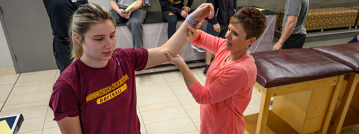 Assistant Professor Anita Gust works with a student's arm, showing techniques.