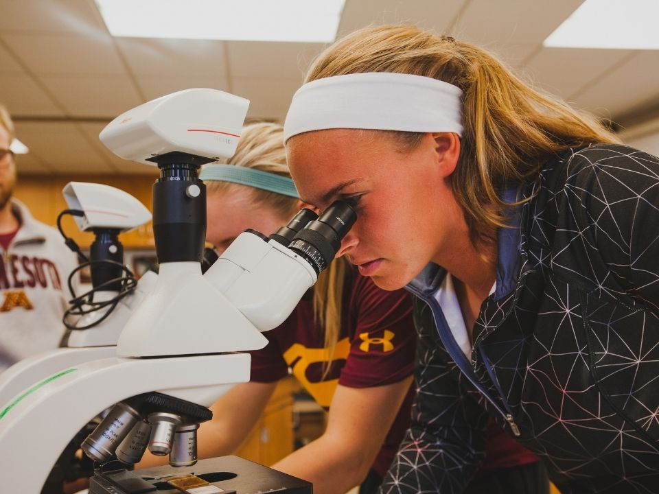 student looking at microscope