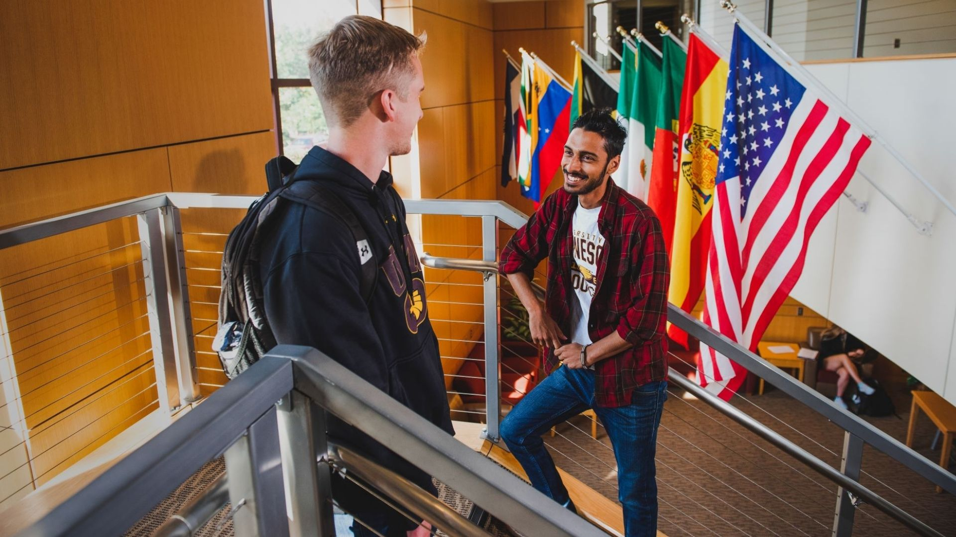 student talking in front of international flags