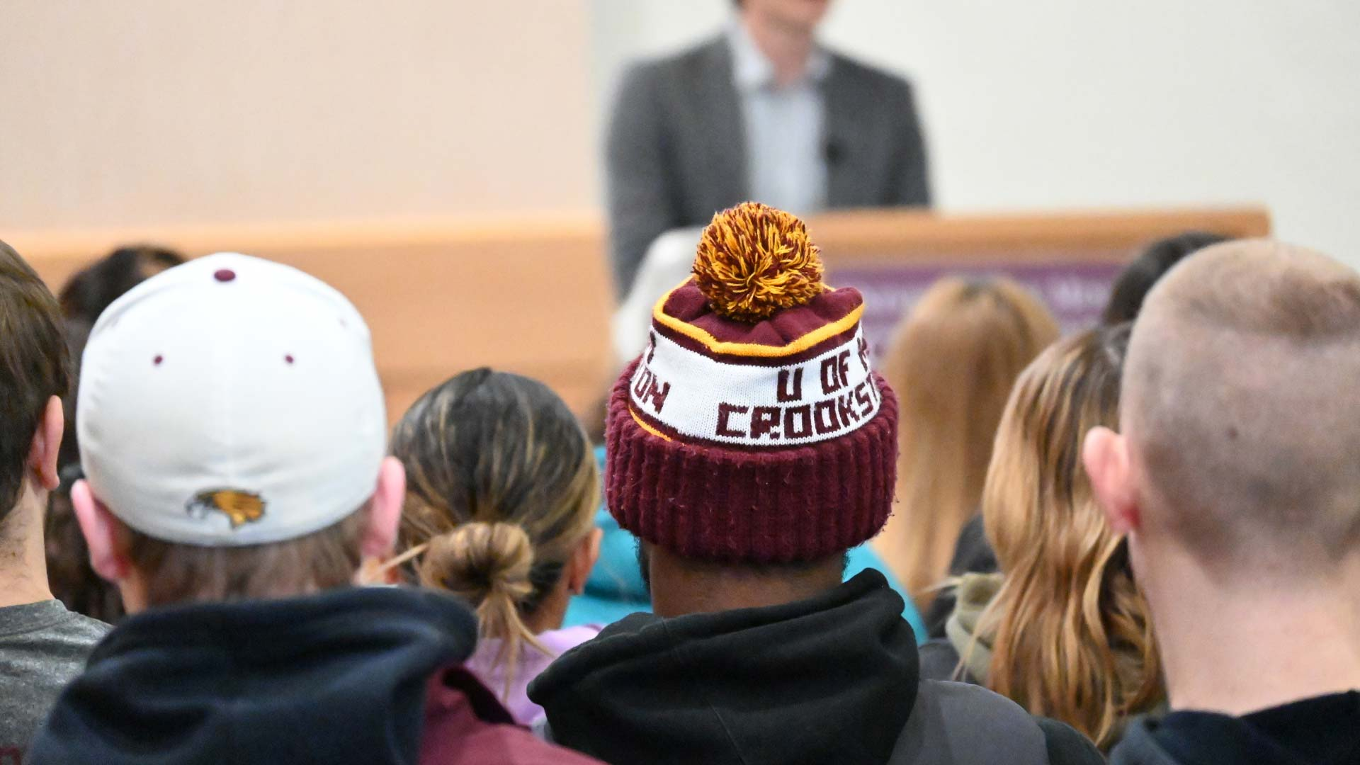 students sitting in bede ballroom, one with a U of MN Crookston knit hat