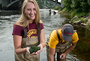 Two Natural Resources students wading in the river taking water samples.