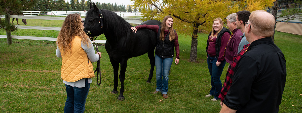 Agriculture Education students and instructors with a black horse, talking outside of the University Teaching and Outreach Center pasture.