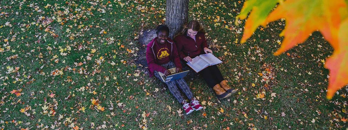 Two students sitting by a tree during the fall