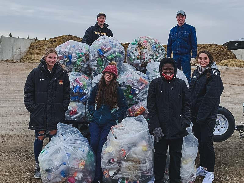 Students with bags of aluminum cans for recycling