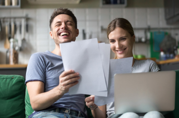 A man and woman sitting on a couch in an apartment on their computer, going through paperwork and laughing