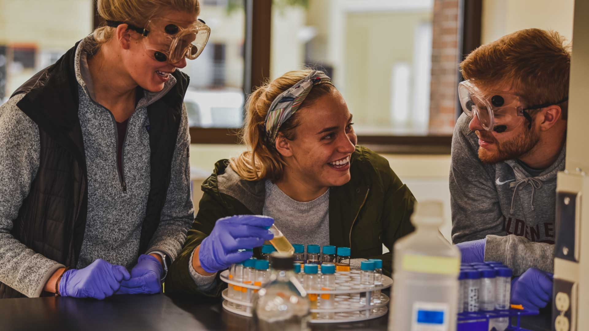 Three students in the Center for Collaborate Research Lab with chemistry tools.