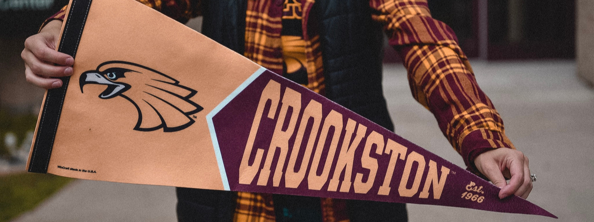 Student holding a crookston pennant flag