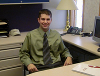 An image of a graduate student in his office
