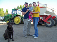A small family gathered in front of a tractor