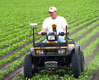 A farmer irrigating crops on a 4 wheeler
