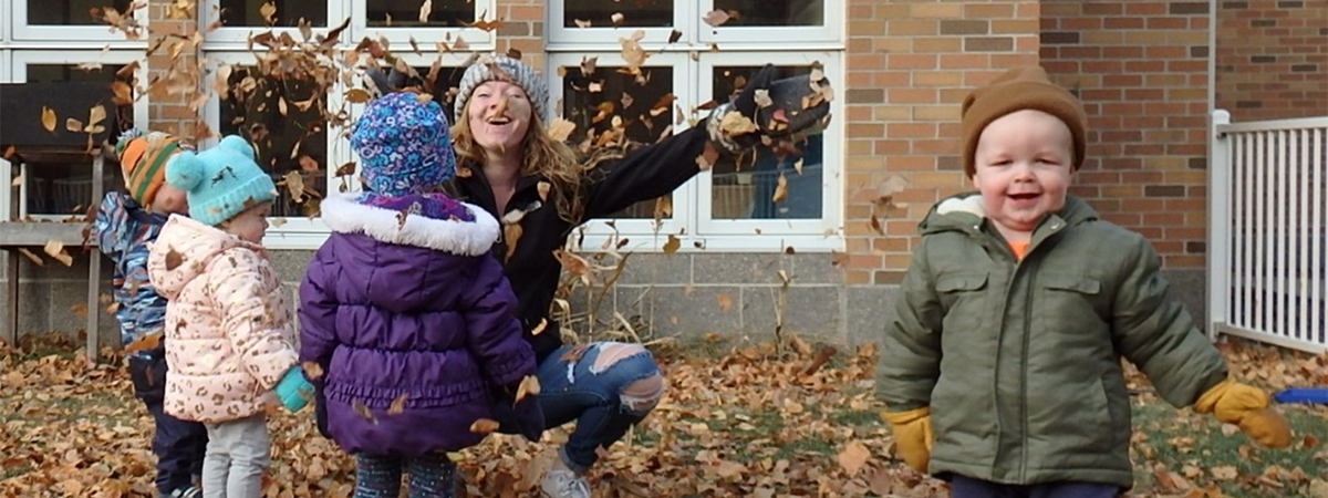Four children with a teacher outside the Early Childhood Development Center during the fall throwing leaves into the air with smiles on their faces.