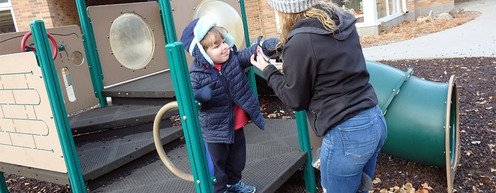 Teacher helping put mittens on a determined toddler at the Early Childhood Development Center play space.