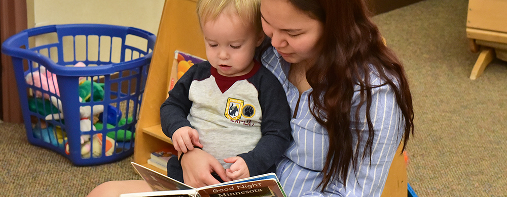 Early Childhood teacher reading to a toddler aged child.