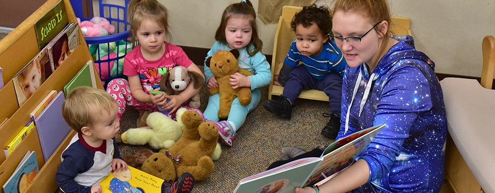 Teacher reading to toddlers at the ECDC.