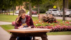 Eleora DeMuth sitting outside the Sargeant Student Center at a picnic table studying.