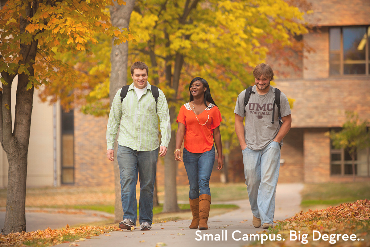 Three students walking on the University of Minnesota Crookston campus during the fall. Small Campus. Big Degree. TM