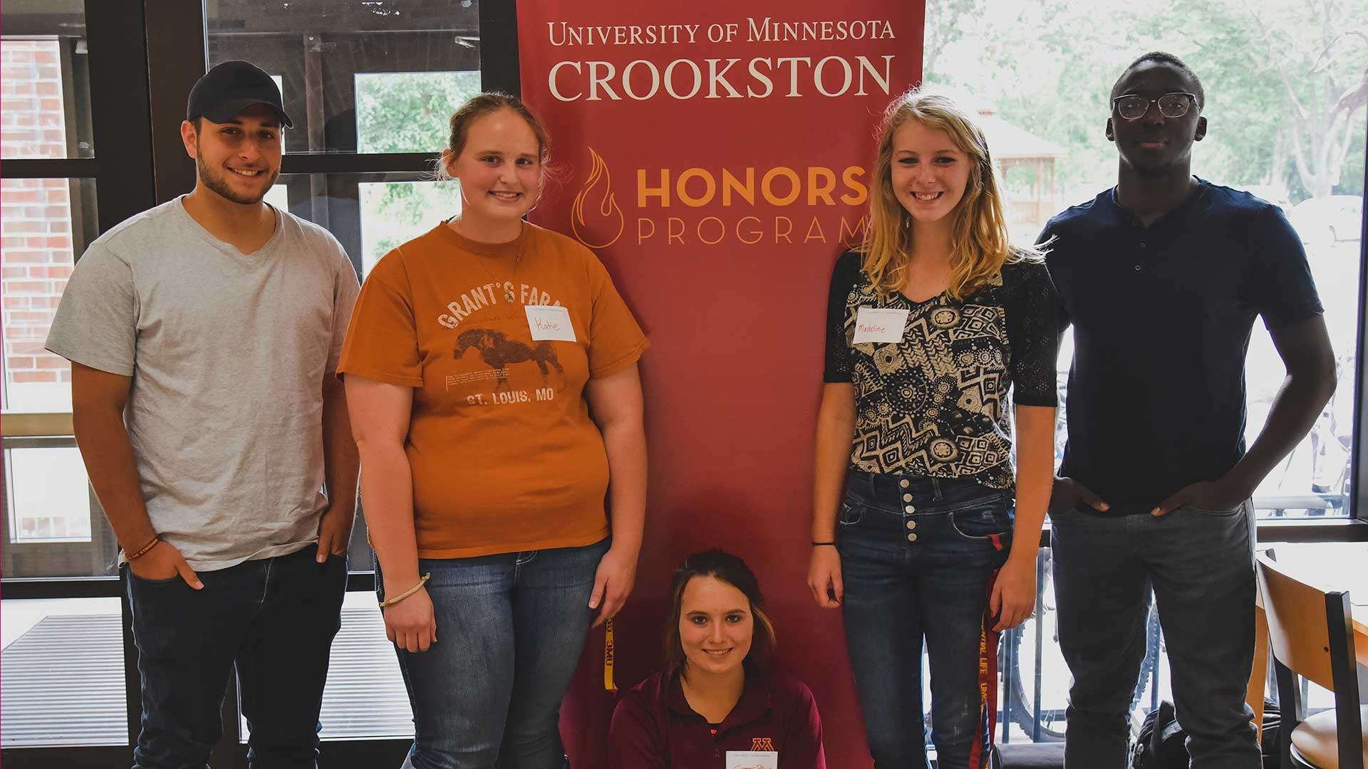 Students in the Honors Program standing by a banner in the Prairie Room