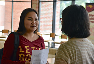 Soo-Yin Lim-Thompson talking to an honors student.
