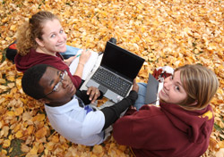 Three students in the fall leaves