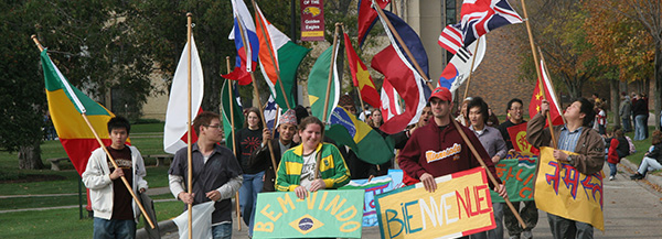 Numerous international students walking in the UMC Homecoming parade holding welcome signs in each of their native languages.