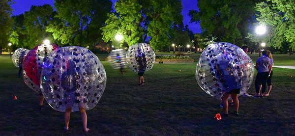 Students taking part in a Knockerball tournament on the UMC Mall in the late evening.