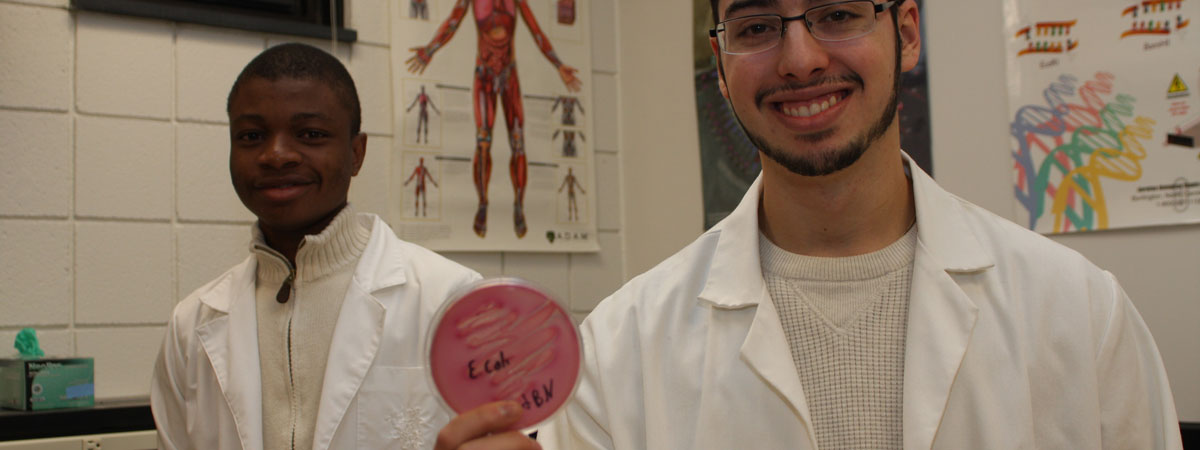 Two students holding a petri dish