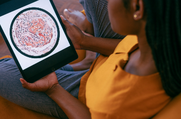 woman sitting on a tablet computer looking at an anatomy of a cell