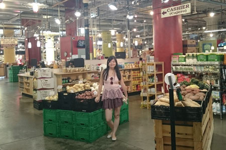 A student standing in a food market