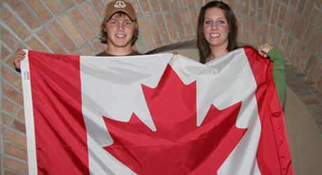 Image of two students holding canada's flag