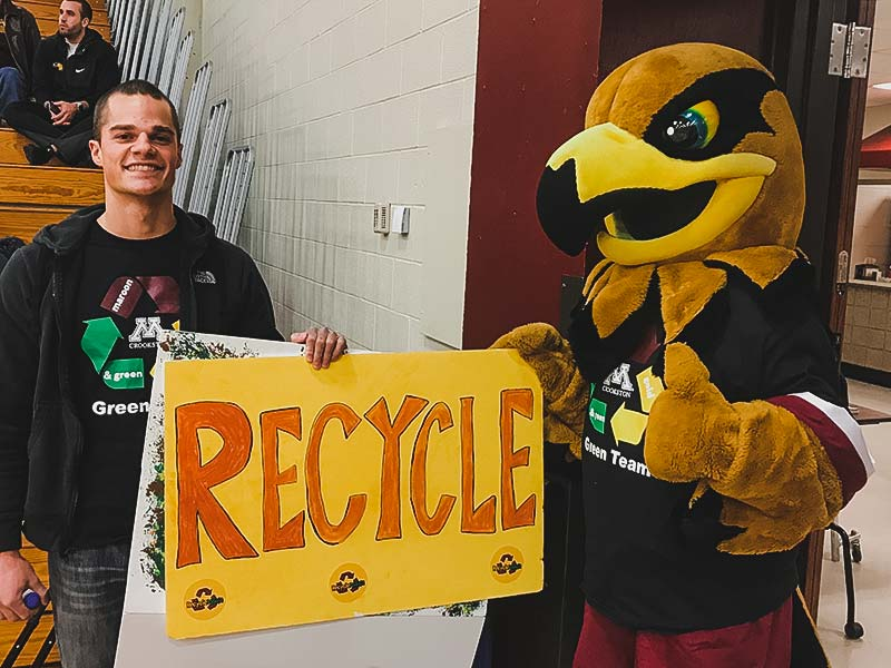 Regal the Eagle and a student at a home basketball game holding a big recycle sign