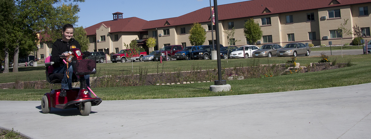 UMC Student riding a mobility scooter across campus.