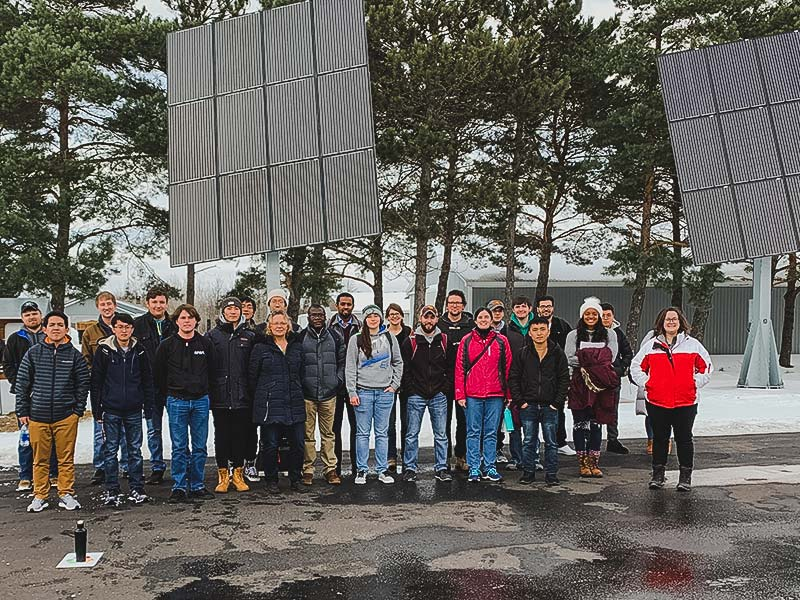 A group of students with large solar panels behind them