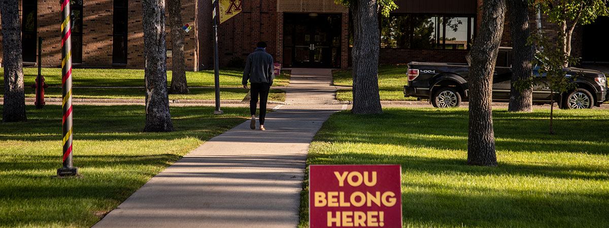 """Campus Mall with student walking to class by a """"You Belong Here"""" sign"""