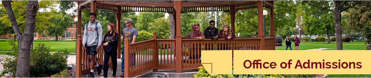 Several students walking on the Campus Mall in and around the Peterson Gazebo on a fall day.