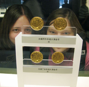 Two students looking at gold coins