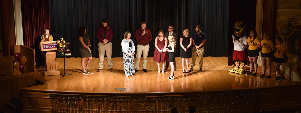 The Royal Court standing on Kiehle Auditorium's stage during Homecoming Coronation