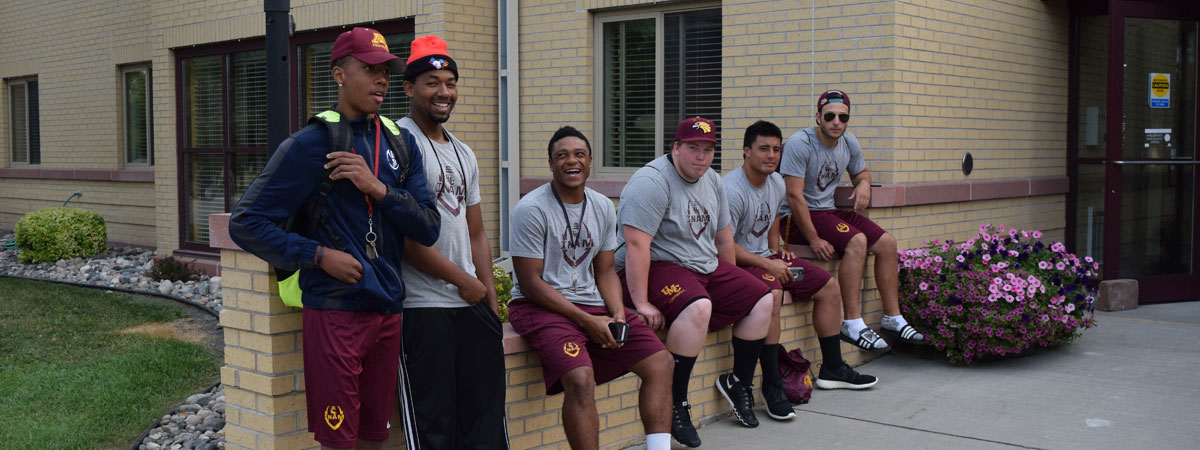 Group of UMC Football players ready to help new students move in.
