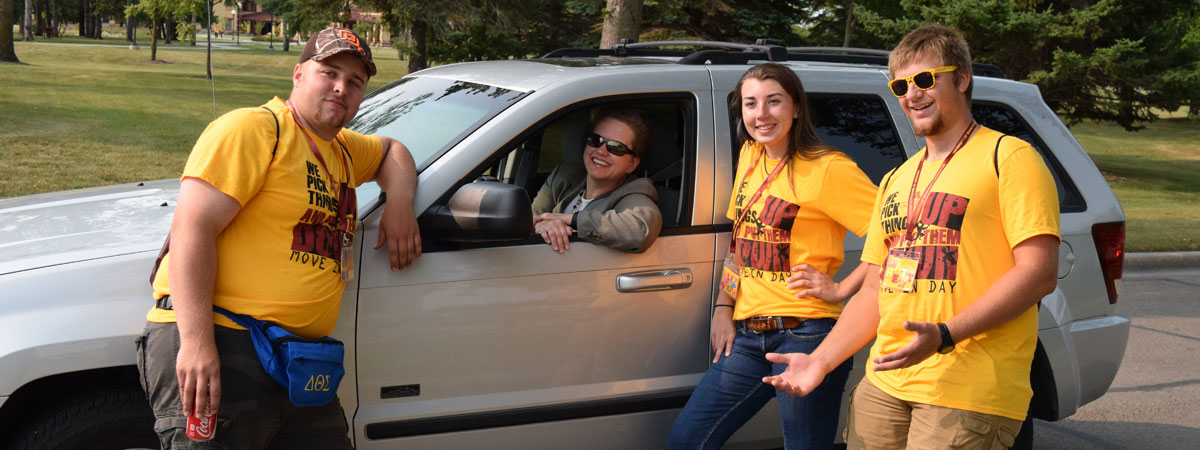 UMC SOS leaders welcoming cars as they drive into campus.