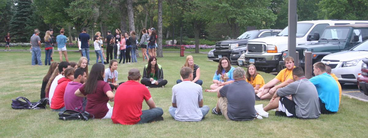 New UMC students in orientation groups in the grassy area outside Kiehle Building.