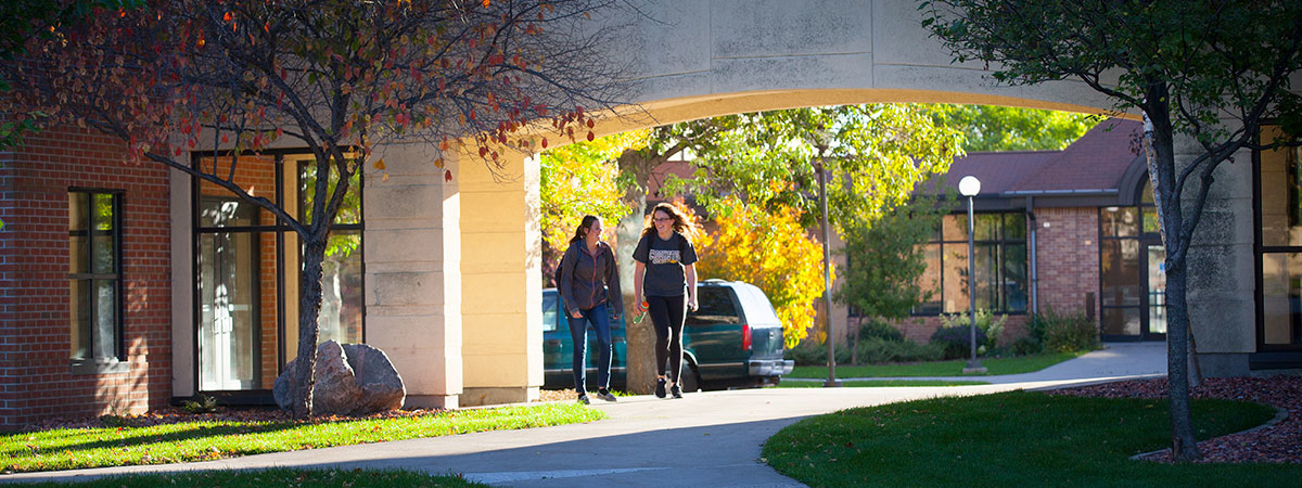 Two female students walking between Hill and Selvig Hall during the fall.