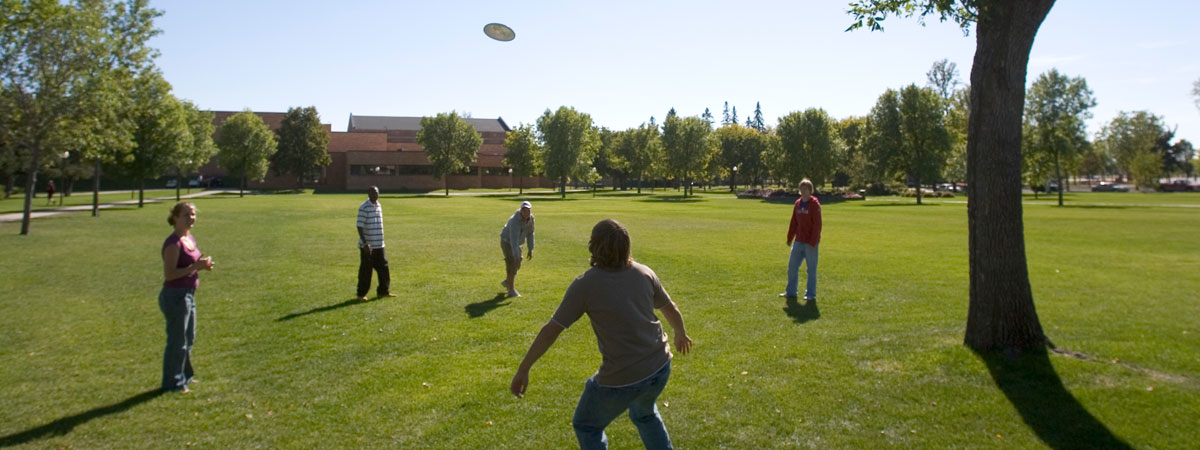 Students playing frisbee on the campus Mall