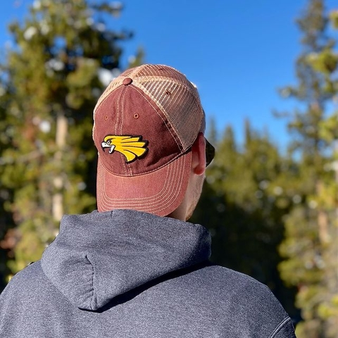 Student standing with backwards Golden Eagle hat