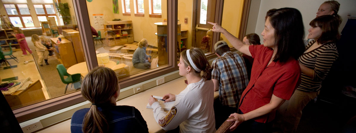 Teacher and students observing children through a one way glass